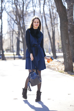 Full body. Portrait of a young beautiful woman in blue coat with a bag walking in spring park Banco de Imagens - 120993238