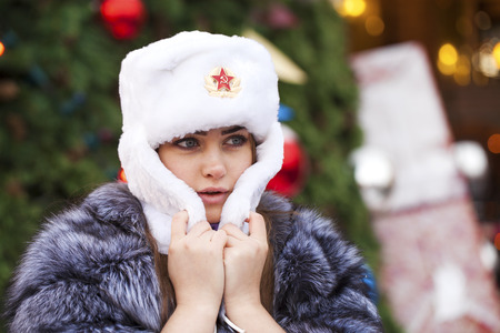 Russian beauty. Portrait of a young beautiful girl in a white hat with a fur hat against a red square in Moscow Standard-Bild