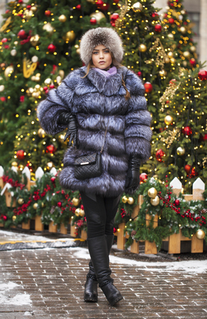 Full length portrait of a girl in an extravagant blue fur coat on a winter park background
