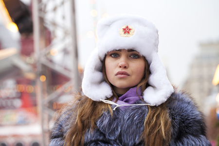 Russian beauty. Portrait of a young beautiful girl in a white hat with a fur hat against a red square in Moscow Stok Fotoğraf - 121332131