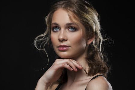 Maquillaje belleza. Cerrar hermosa modelo rubia en retrato de estudio sobre fondo negro aislado