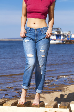Front view of a long women legs posing with blue jeans, summer outdoors