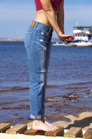 Widok z przodu długich nóg kobiet pozujących w niebieskich dżinsach, lato na zewnątrz