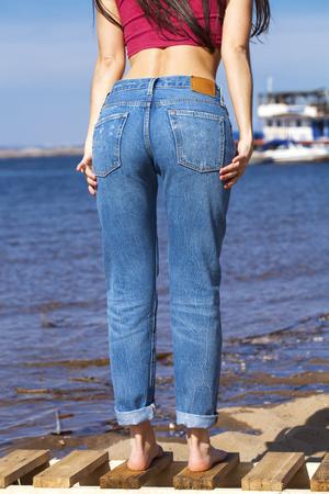 Vorderansicht von langen Frauenbeinen, die mit Blue Jeans posieren, Sommer im Freien
