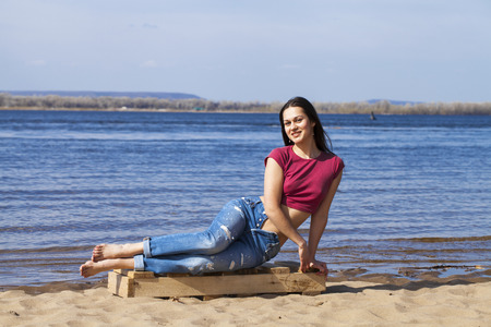 Full-length portrait of a young beautiful girl in trendy jeans posing against the backdrop of the Volga River