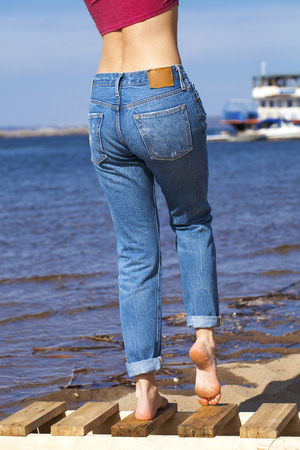 Front view of a long women legs posing with blue jeans, summer outdoors Banque d'images