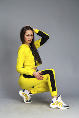Portrait of a young beautiful brunette woman in yellow tracksuit, isolated on gray background 写真素材