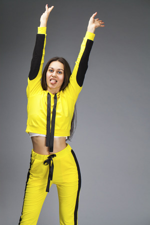 Portrait of a young beautiful brunette woman in yellow tracksuit, isolated on gray background 版權商用圖片