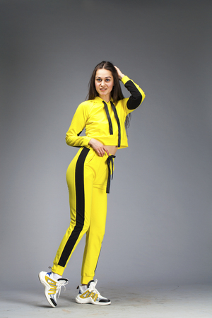 Portrait of a young beautiful brunette woman in yellow tracksuit, isolated on gray background Reklamní fotografie