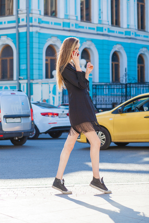 Close up, sexy attractive young blonde woman in black jacket walking in summer street 免版税图像