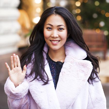 Szczęśliwa azjatycka kobieta w zimowym płaszczu ze sztucznego futra, chodząca po czerwonym placu, Rosja