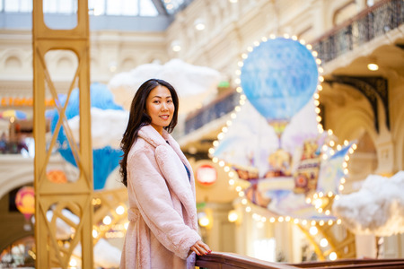 Happy asian woman in winter coat from faux fur, walking on red square, Russia