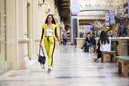 Retrato de una joven hermosa en un top blanco y pantalones deportivos amarillos posando en un centro comercial Foto de archivo