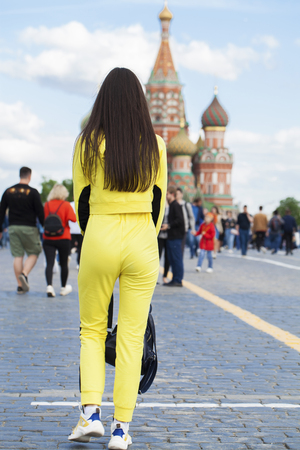 Full length portrait of a young beautiful tourist girl sitting on a red square in Moscow 스톡 콘텐츠