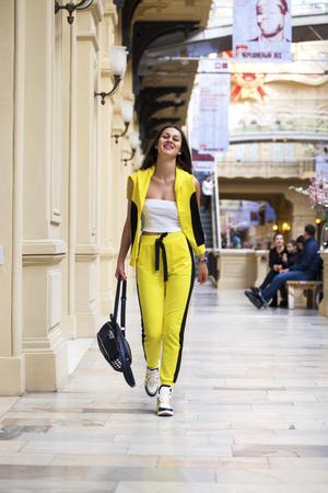 Retrato de una joven hermosa en un top blanco y pantalones deportivos amarillos posando en un centro comercial