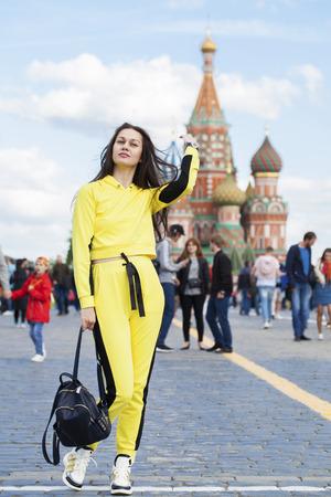 Retrato de cuerpo entero de una hermosa joven turista sentada en una plaza roja en Moscú Foto de archivo