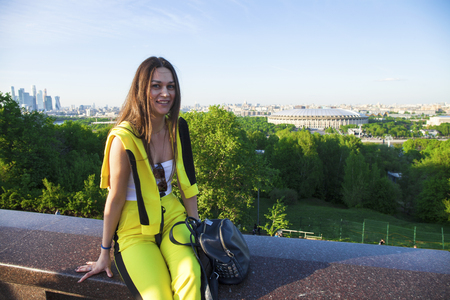 A young beautiful girl in a yellow jumpsuit sits on the railing against the backdrop of the Sparrow Hills in Moscow 免版税图像