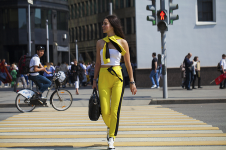Full length portrait of a young beautiful brunette woman in yellow jumpsuit posing on the street