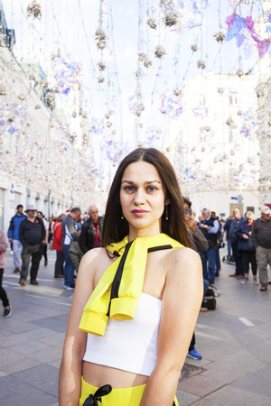 Portrait of a young beautiful tourist posing against the background of garlands on Nikolskaya street in the center of Moscow 版權商用圖片