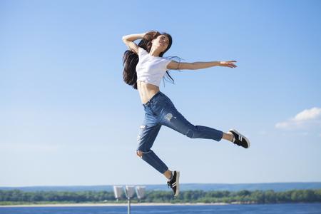 Chica de cuerpo entero en un salto. Joven hermosa mujer morena posando contra el cielo azul brillante clima soleado
