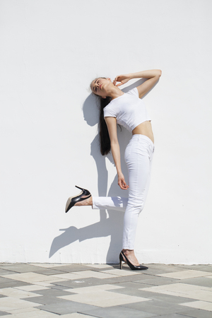 Model tests. Young beautiful brunette girl posing against a white wall in bright sunny weather Standard-Bild