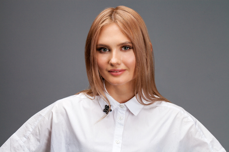 Closeup portrait of a young beautiful blonde woman in a white shirt isolated on gray background