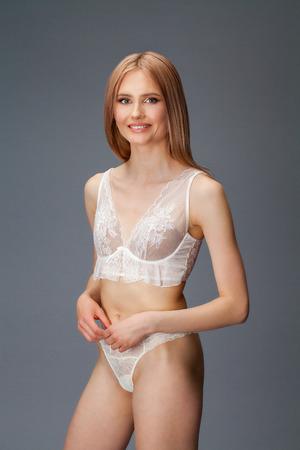 Giovane donna bionda sexy che posa in biancheria intima bianca sopra il fondo grigio scuro della parete
