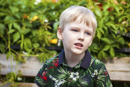 Blonde Little boy in green flowers shirt in the summer park