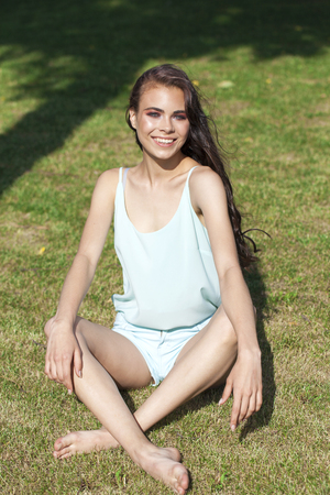 Young beautiful brunette girl in a turquoise blouse posing sitting on a green lawn in a summer park Stock Photo - 124628405