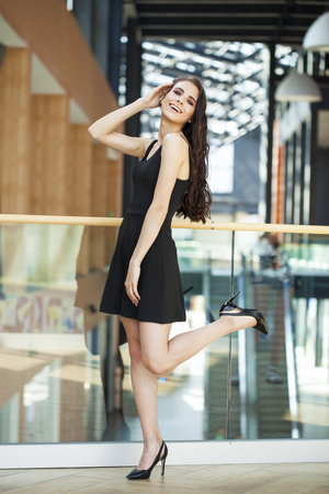 Full body portrait of a happy young brunette woman in black dress, indoor
