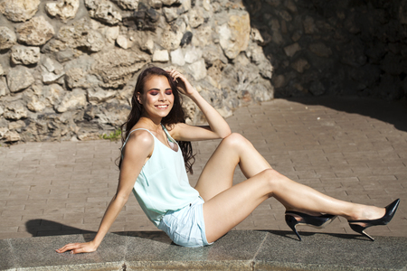 Portrait in full growth, young beautiful brunette woman in a blue blouse and shorts, summer park outdoors Stock Photo