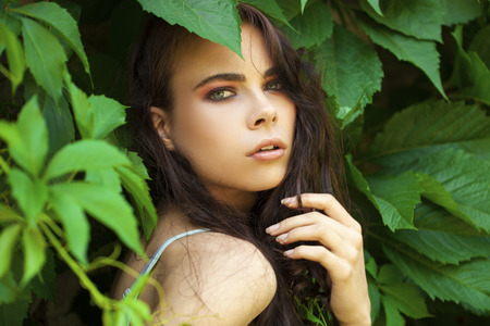Close up portrait of a young beautiful girl in green ivy foliage Stock Photo