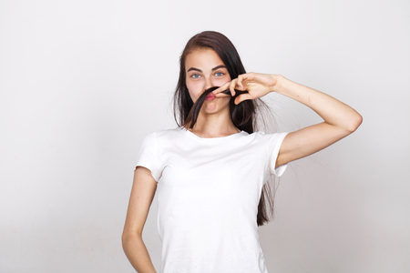 Young beautiful girl with a mustache from their hair in the studio on a white background