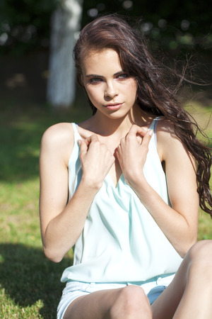 Young beautiful brunette girl in a turquoise blouse posing sitting on a green lawn in a summer park