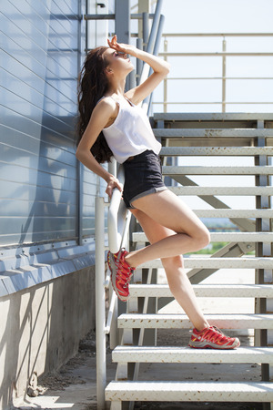 Street fashion women. Full-length portrait young beautiful model in shorts posing on the stairs, summer outdoors