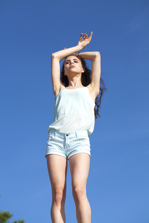 Young beautiful girl in a turquoise blouse posing against the blue sky