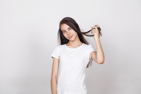 Close up portrait of a pretty young brunette schoolgirl smiling charmingly, isolated on white wall background