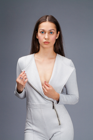 Sexy fashion brunette woman in gray leather suit posing in the studio on a gray background Banco de Imagens