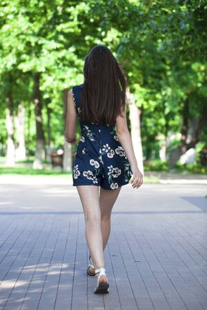 Young beautiful brunette woman in a blue short dress walking on the road, summer street outdoors Banco de Imagens