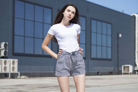 Portrait of a pretty young brunette model in white summer blouse and jeans, summer street outdoors