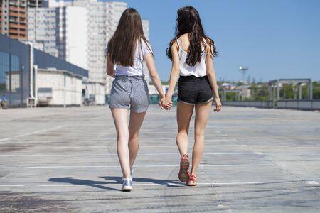 Happy Two girlfriends walking on summer street, outdoors