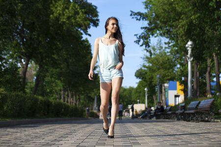 Full body portrait of a happy young brunette woman walking in black dress, indoor