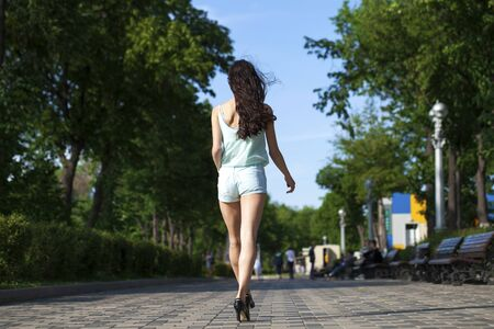 Portrait in full growth, young beautiful brunette woman in a blue blouse and shorts walking on the street, summer park outdoors