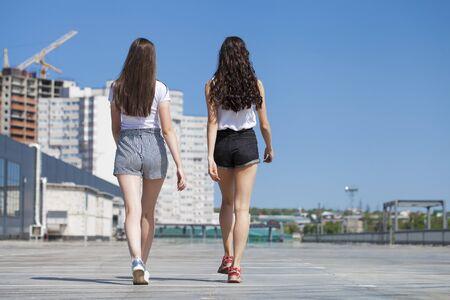 Dos amigas felices caminando en la calle de verano, al aire libre Foto de archivo