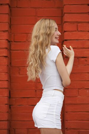 Back view portrait of a young beautiful blonde model in white shorts and a vest posing against a beautiful brick wall