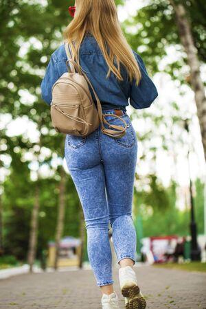 Corps entier - Vue arrière Jeune fille blonde en jeans bleu marchant dans le parc d'été