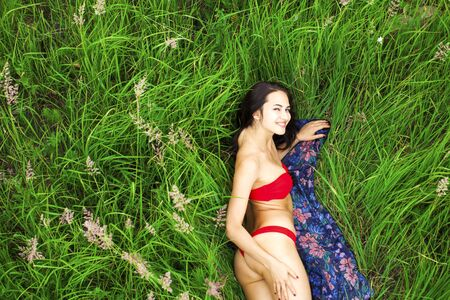 Young beautiful sexy girl in a red bathing suit lying on the grass top view Stock Photo