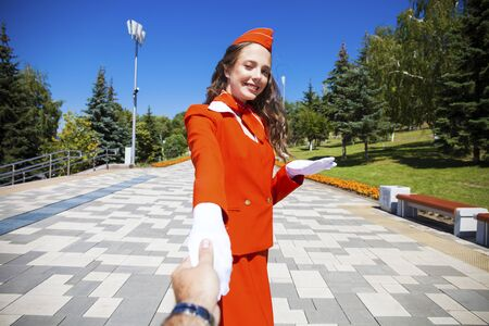 Follow me beautiful young stewardess in red uniform