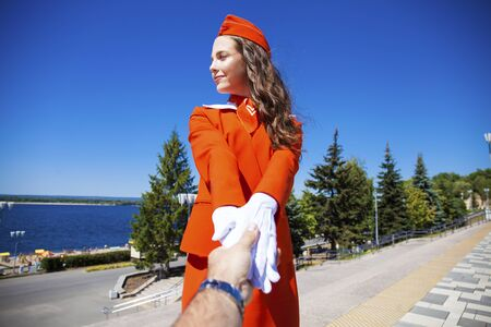 Follow me beautiful young stewardess in red uniform