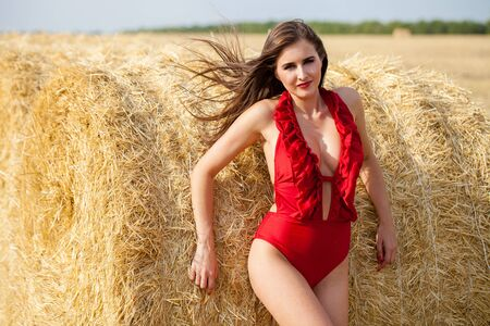 Young beautiful brunette model in red bikini in the hayloft